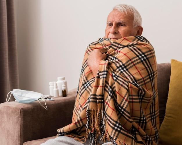 Старик среднего размера испытывает озноб