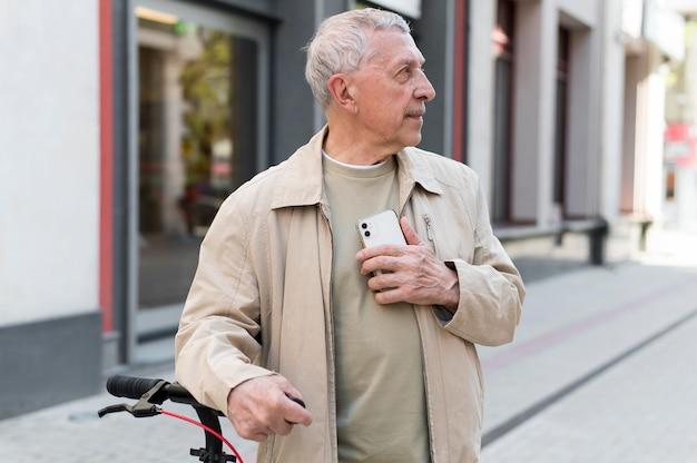 Medium shot old man holding phone