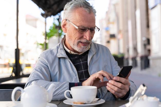 Medium shot old man holding smartphone