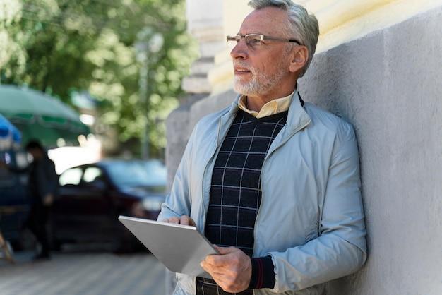 Medium shot old man holding tablet