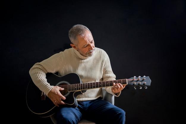 중간 샷 노인 기타 연주
