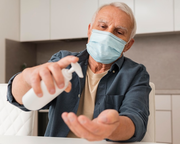 Medium shot old man pouring disinfectant
