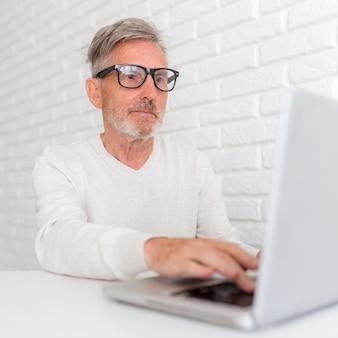Medium shot old man typing on keyboard