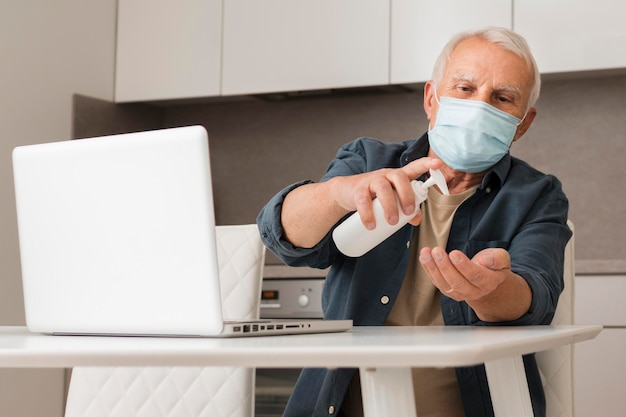Medium shot old man using disinfectant