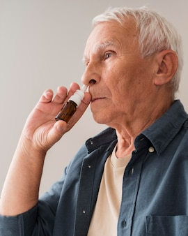Medium shot old man using nasal spray