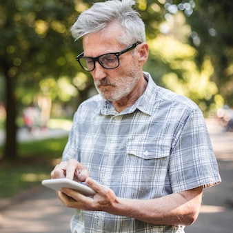 Средний выстрел старика, использующего смартфон