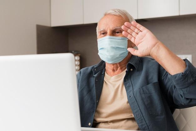 ノートパソコンで手を振っているミディアムショットの老人