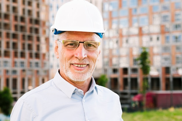 Medium shot old man with glasses and safety helmet