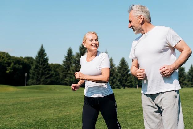 Medium shot old people running outdoors