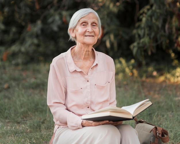 Средний выстрел старая женщина, держащая книгу