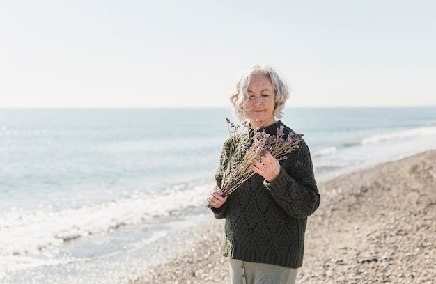 Medium shot old woman holding flowers