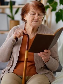중간 샷 늙은 여자 읽기 책
