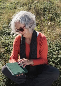 Medium shot old woman with book outdoors