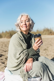 Medium shot old woman with coffee cup