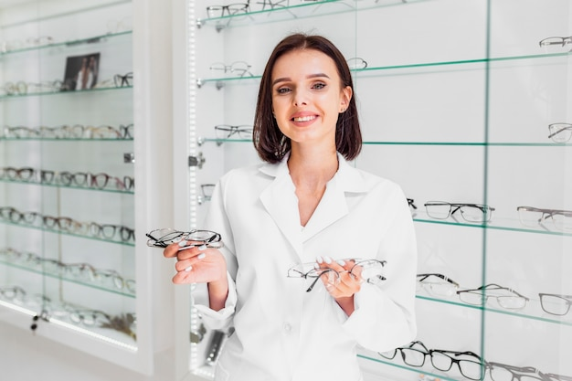 Medium shot of optician holding glasses frames