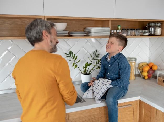 キッチンでミディアムショットの親と子