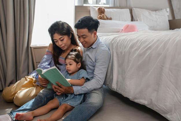 ミディアムショットの両親と本を持つ少女