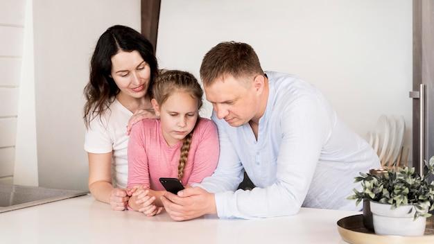 Средний снимок родителей и девочки с телефоном
