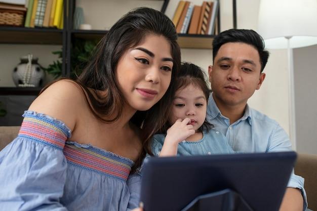 ミディアムショットの両親とタブレットを持つ女の子