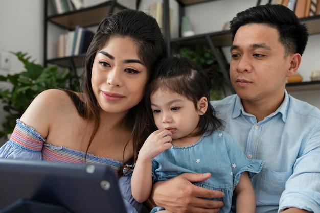 ミディアムショットの両親と女の子