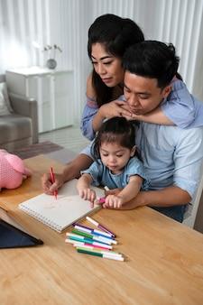 ミディアムショットの両親と子供が机に