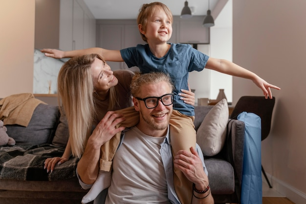 自宅でミディアムショットの両親と子供