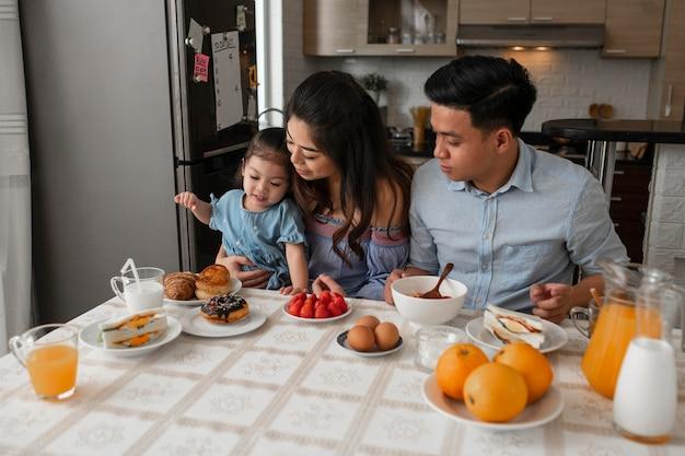 ミディアムショットの両親と子供がテーブルに