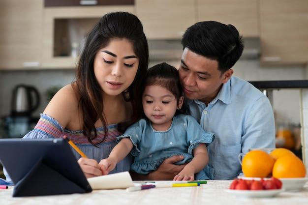 Средний снимок родителей и малыша за столом