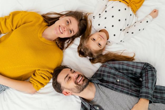 ベッドの上面図でミディアムショットの両親と子供