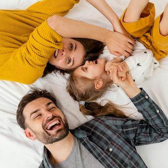 Средний снимок родителей и ребенка в постели, вид сверху
