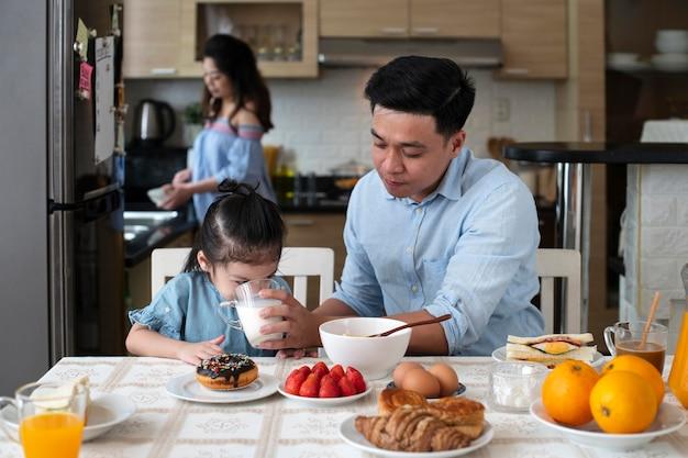 キッチンでミディアムショットの両親と子供