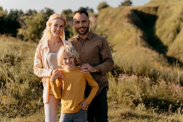 Средний снимок родителей и малыша позируют