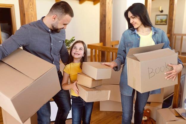 ミディアムショットの親とボックスを持つ子供