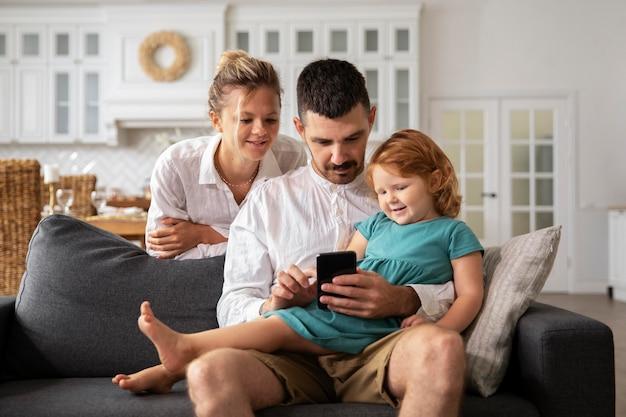 Родители среднего кадра и ребенок с устройством
