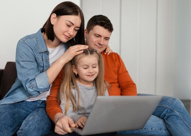 ミディアムショットの親とラップトップを持つ子供