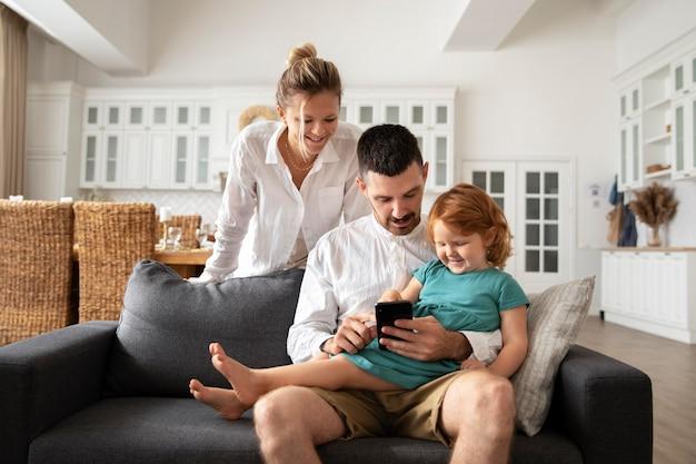 Средний снимок родителей и ребенка с телефоном