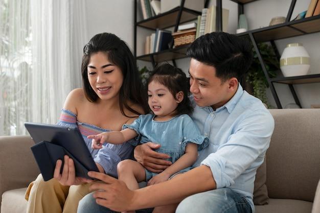 ミディアムショットの親と子供とタブレット