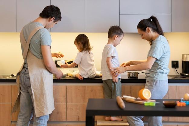 중간 샷 부모와 아이들이 주방