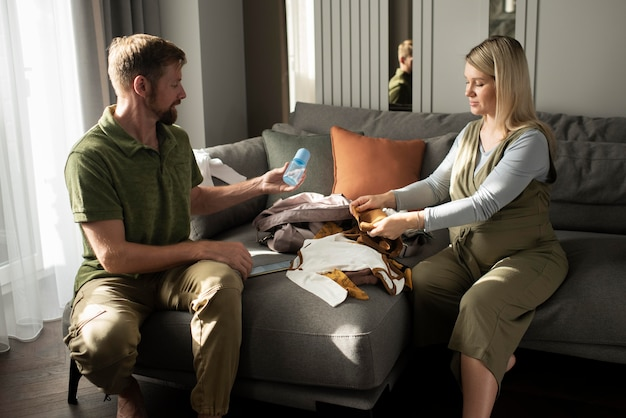 Medium shot parents to be with baby clothes