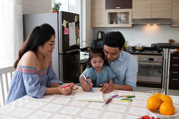 Medium shot parents and kid drawing