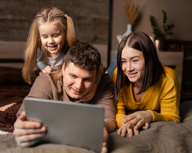 Medium shot parents and kid with tablet