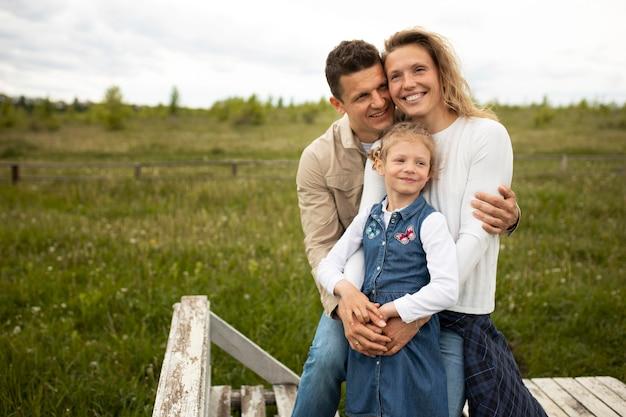 Medium shot parents with kid outdoors