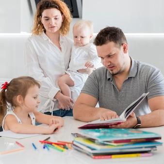 子供向けの本を持つミディアムショットの両親
