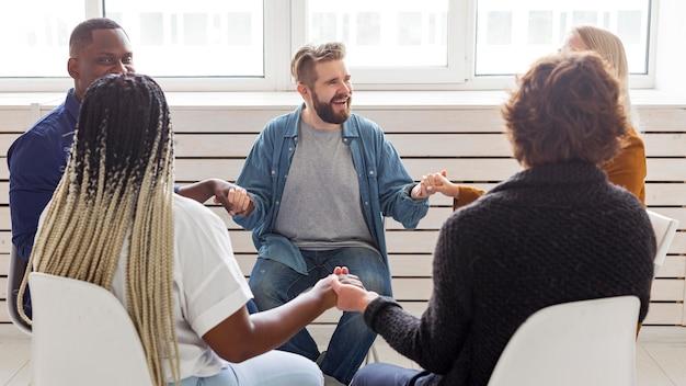 Среднего плана люди, взявшись за руки на встрече