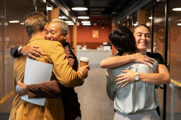 직장에서 포옹하는 중간 샷 사람들