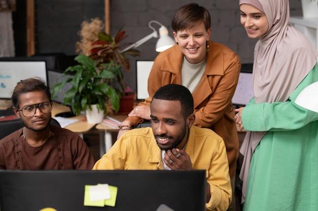 Люди среднего кадра, смотрящие на компьютер
