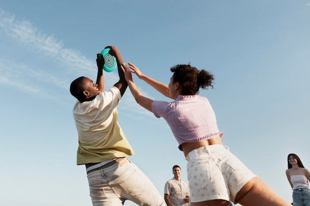 Medium shot people playing at beach low angle