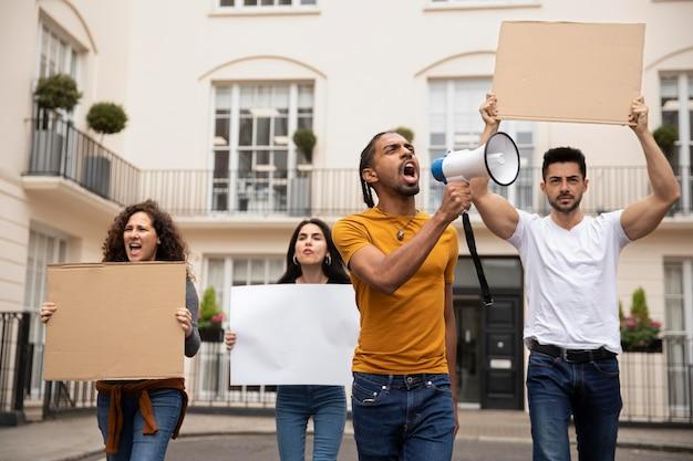 プラカードで抗議するミディアムショットの人々