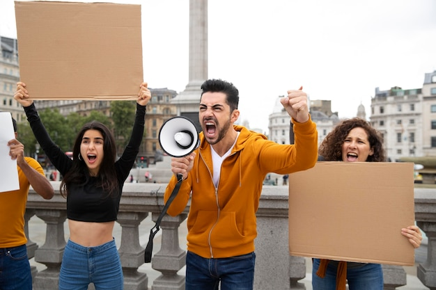 Люди среднего кадра кричат в знак протеста