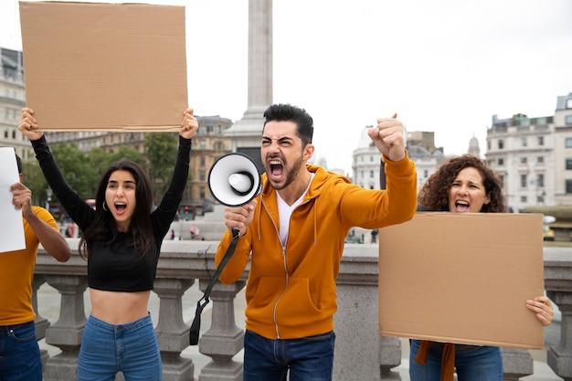 Medium shot people screaming at protest